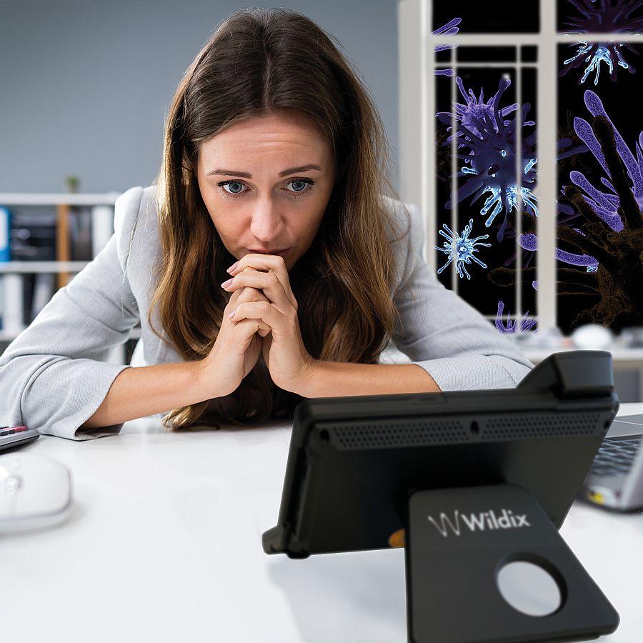 Coronavirus-Angst Frau im Homework warten auf Anruf vor dem WILDIX IP Telefon. Im Freien schwirren Viren.